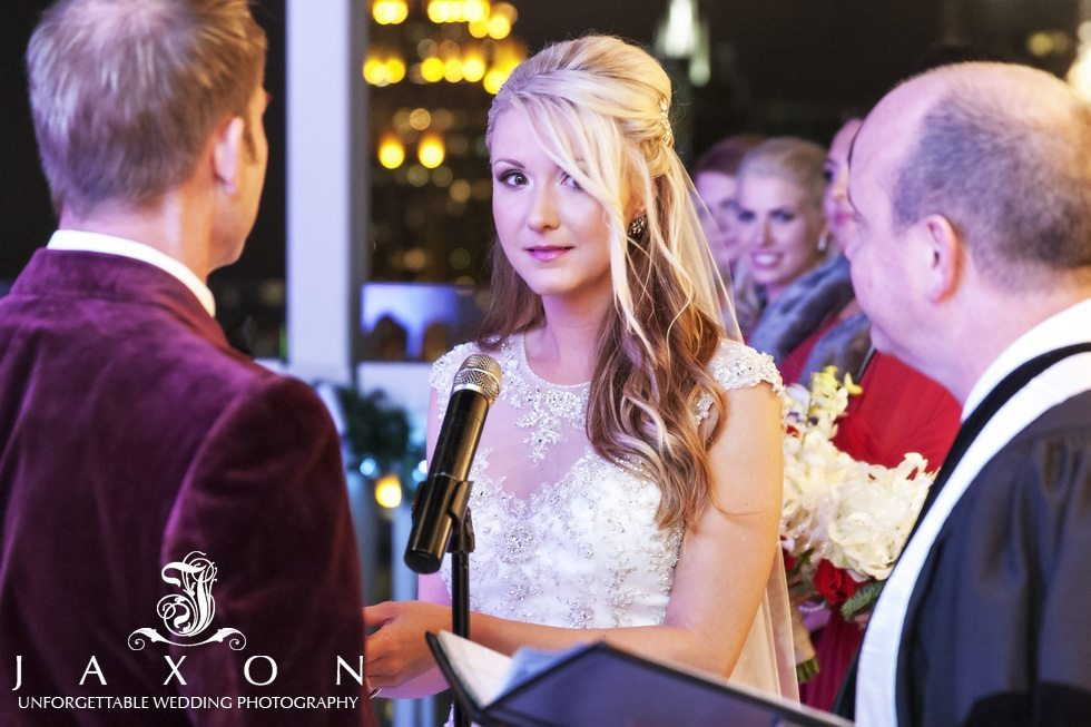Bride smiles with relief as she recites her wedding vows at their Peachtree Club Rooftop wedding