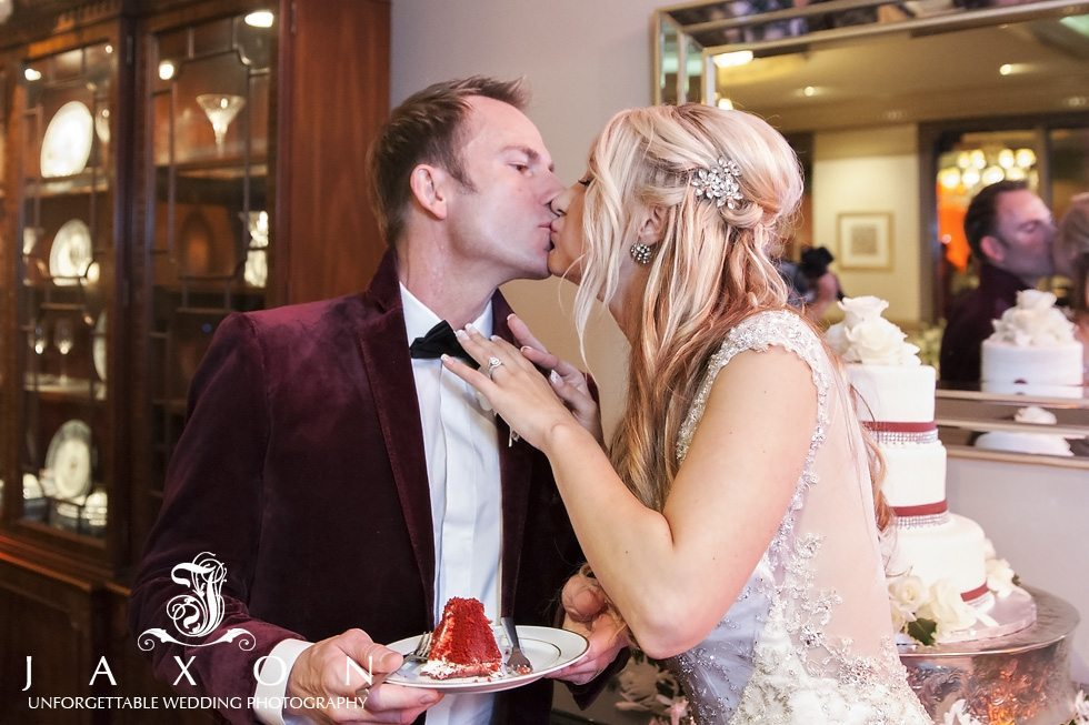 Couple shares a kiss after feeding each other a piece of the red velvet that the groom holds