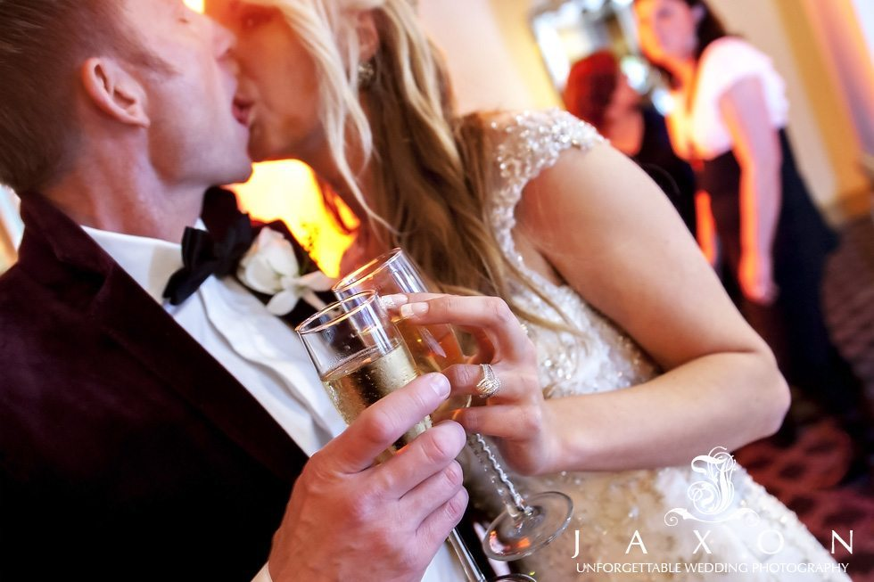 Close up of couples champaign glasses toasting as they kiss in the background