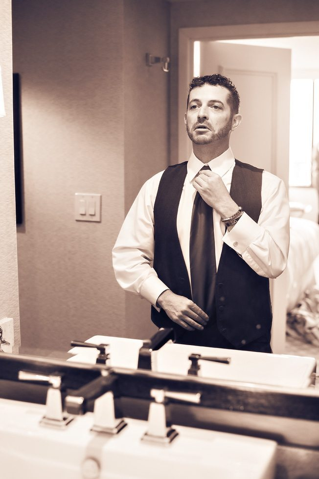 Grooms man adjusts his tie in this sepia toned photograph of him getting ready at the Ritz in Atlanta