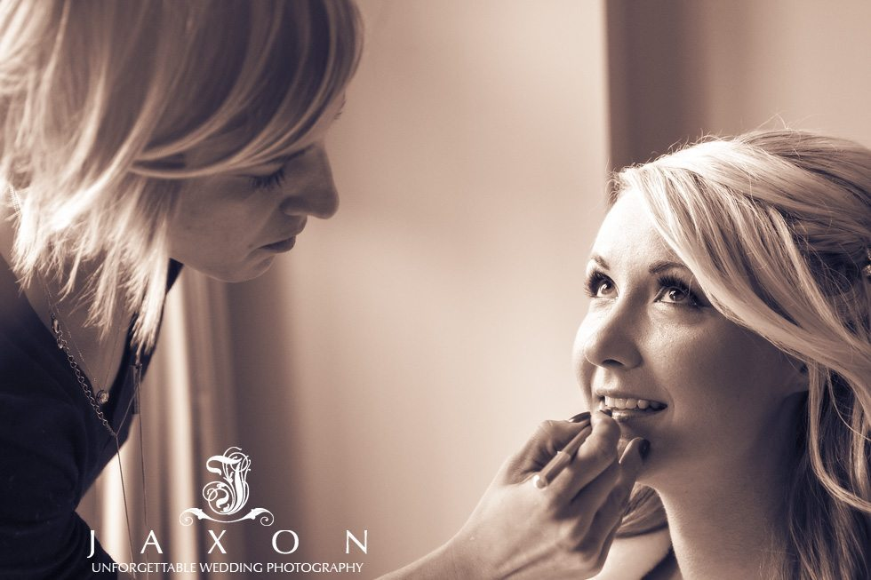 A sepia portrait of a bride having her makeup applied in her suite at the Georgian Terrace Hotel before her wedding