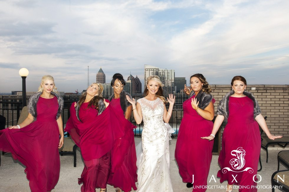 Bridal Party in ankle length maroon dresses and gray fur wraps Rooftop at the Georgian Terrace Hotel strutting their stuff, Downtown Atlanta Skyline in background