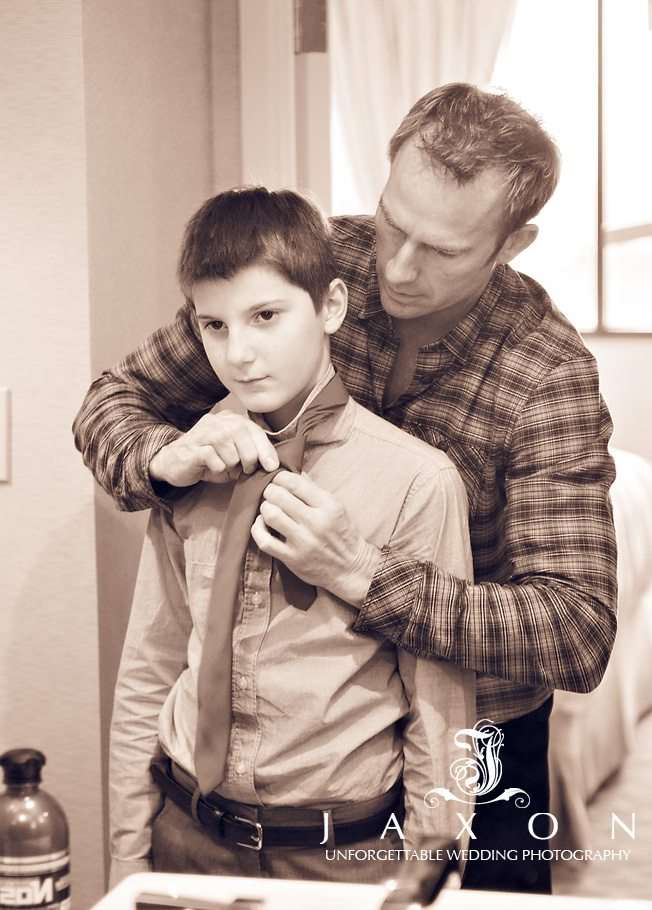 Groom helping junior groomsman tie his tie