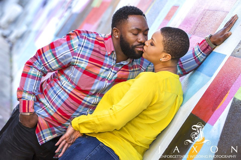 Engagement couple kisses against the colorful walls at North Ave and the beltline