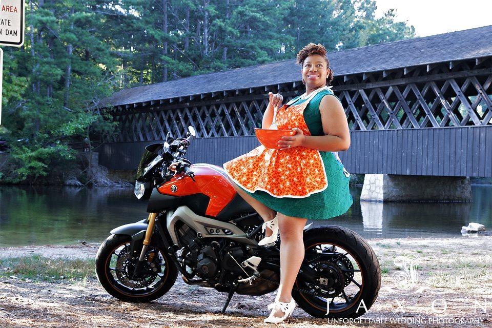 woman sits on motor bike dressed in orange apron