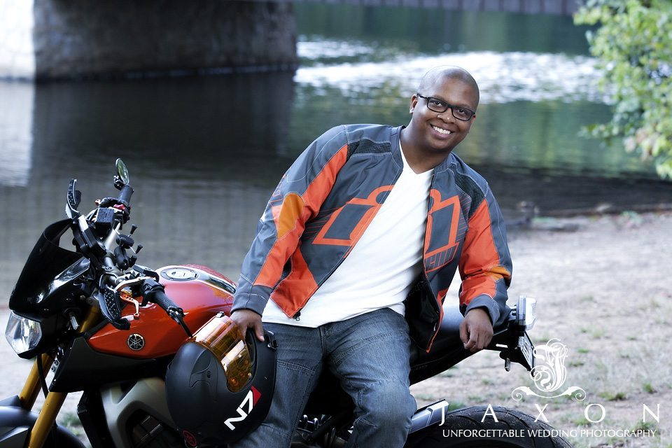 man sits on motor bike next to the covered bridge