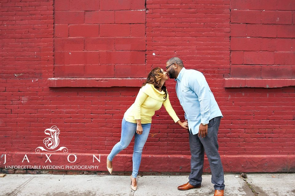 Couple kisses against a backdrop of red brick wall
