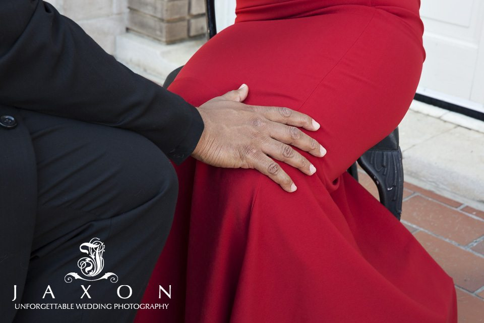 mans hand on woman's knee as the sit on terrace