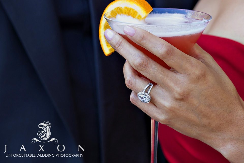 Closeup of woman's hand wearing an engagement ring and holding cocktail