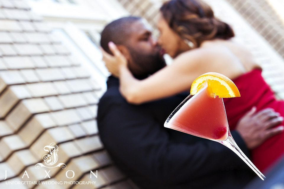 Cocktail glass in foreground of photo with couple kissing in background