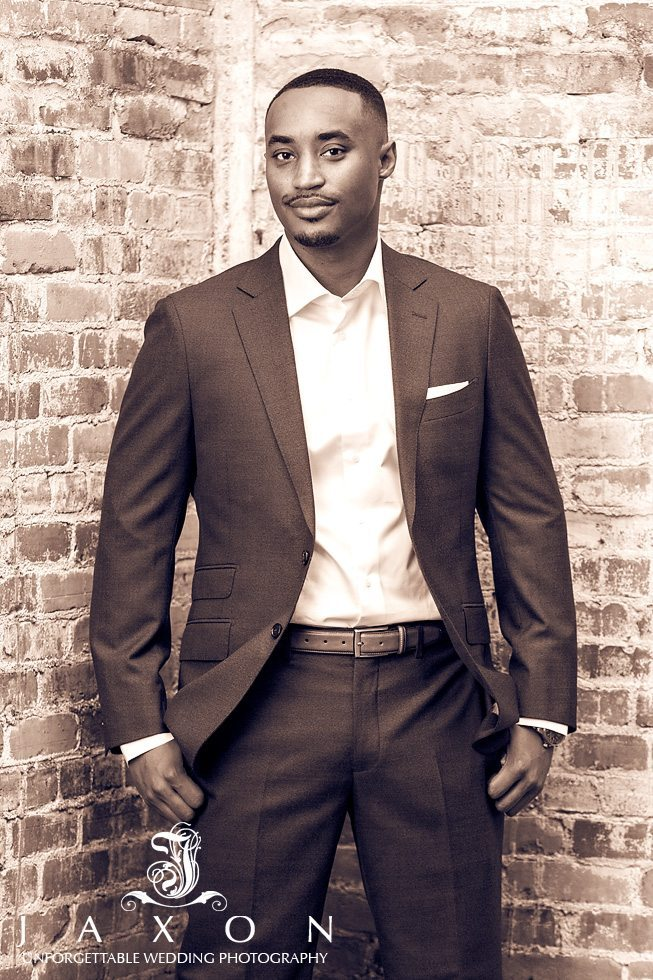 Sepia tone photograph of black male in suite posing agains brick wall