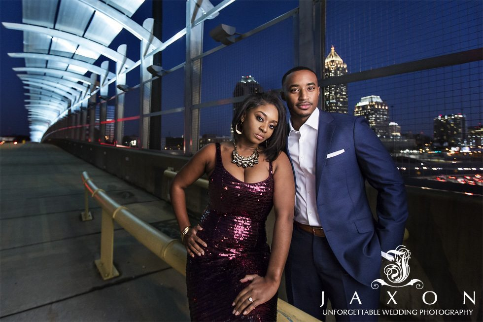 Beautifully dressed young couple he is in a blue suite and she is wearing a metallic spaghetti strap plum dress, adding some sophistication on 17th St Bridge in Atlantic Station Atlanta