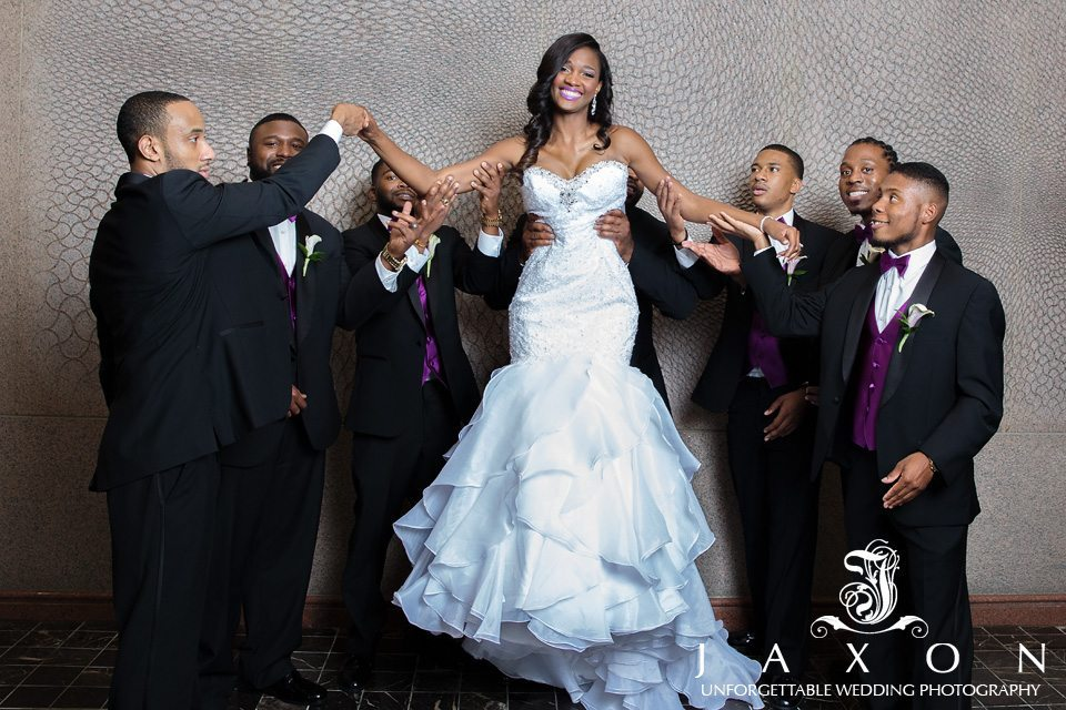 7 groomsmen lifts bride off her feet during their fun photo session after wedding ceremony