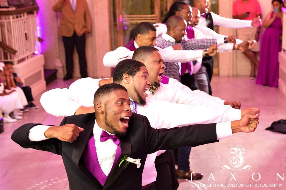 Fraternity brothers perform a dance during wedding reception