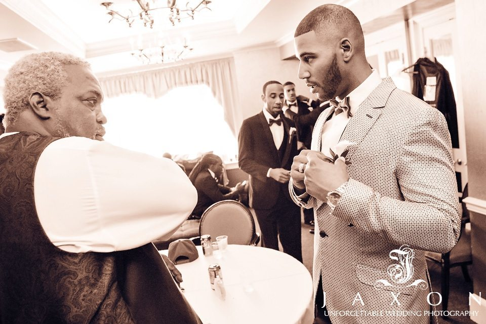 Groom prepares for his wedding and brides dad looks on