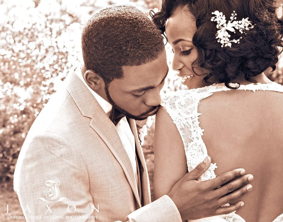 Sepia portrait of groom kissing brides shoulder as she looks on and smile, the heart shaped cutout in the back of dress framed beautifully