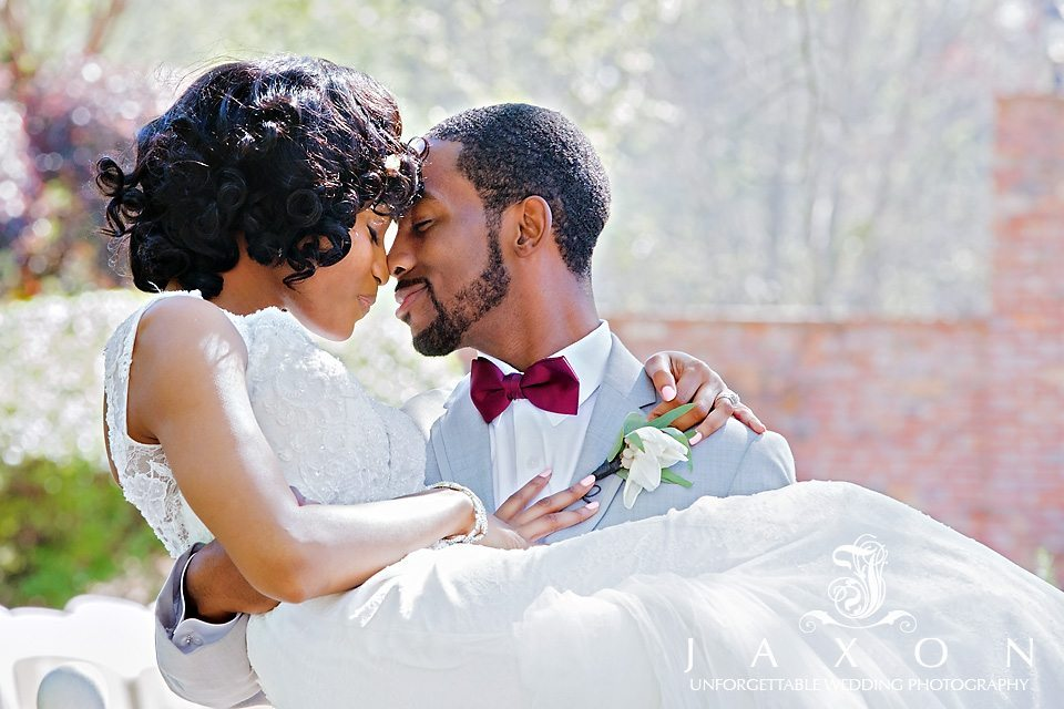 Groom scoops his bride up in his arms in the gardens of the carl house mansion in Auburn GA