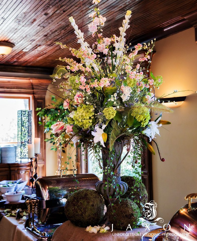 Buffet table floral arrangement with moss covered balls at base of metal urn vase topped with Hydrangeas, tulips, and lilies.