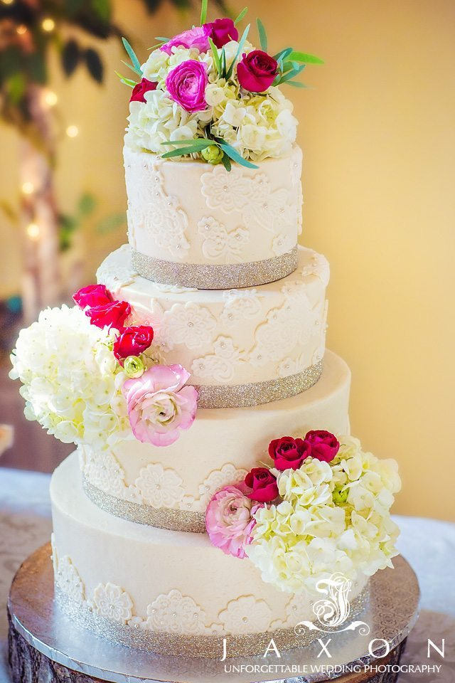 5 tiered white lace brushed embroidered wedding cake with silver bands and accessorized with flowers