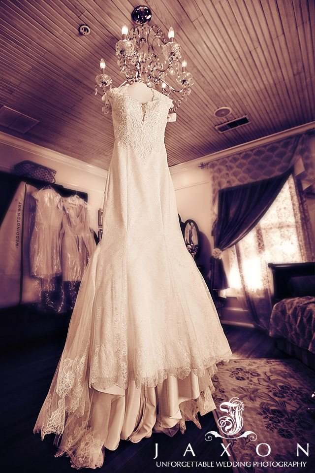 Sepia image of bides wedding dress hanging in the bridal suite before her Carl House Wedding