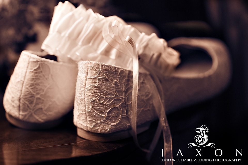 Sepia tone image of the brides lace ballerina flats and garter on table before her Carl House Wedding