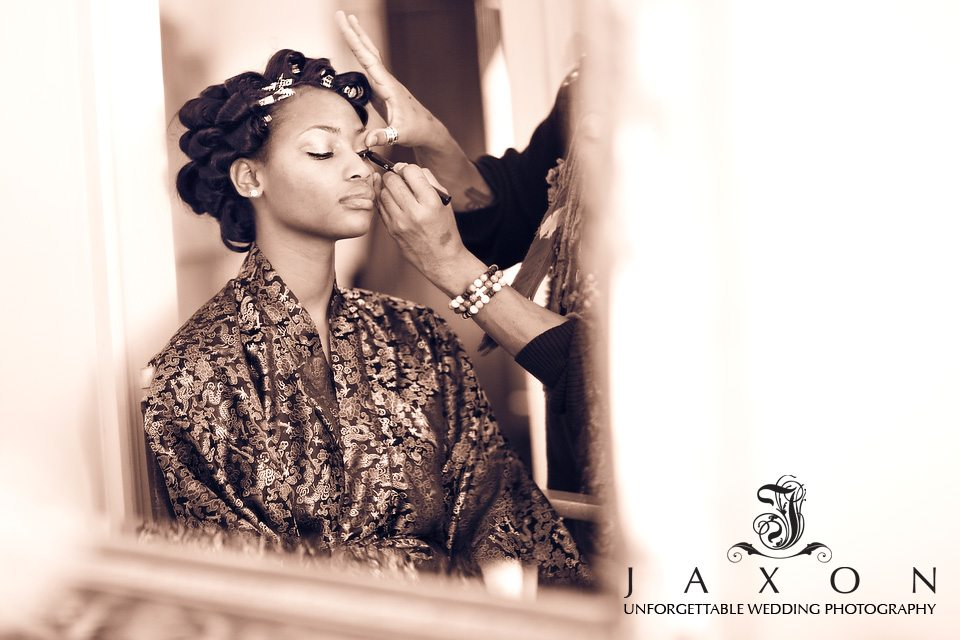 Sepia tone reflection of make up artist applying eyeliner to bride wearing silk robe with rollers in her hair