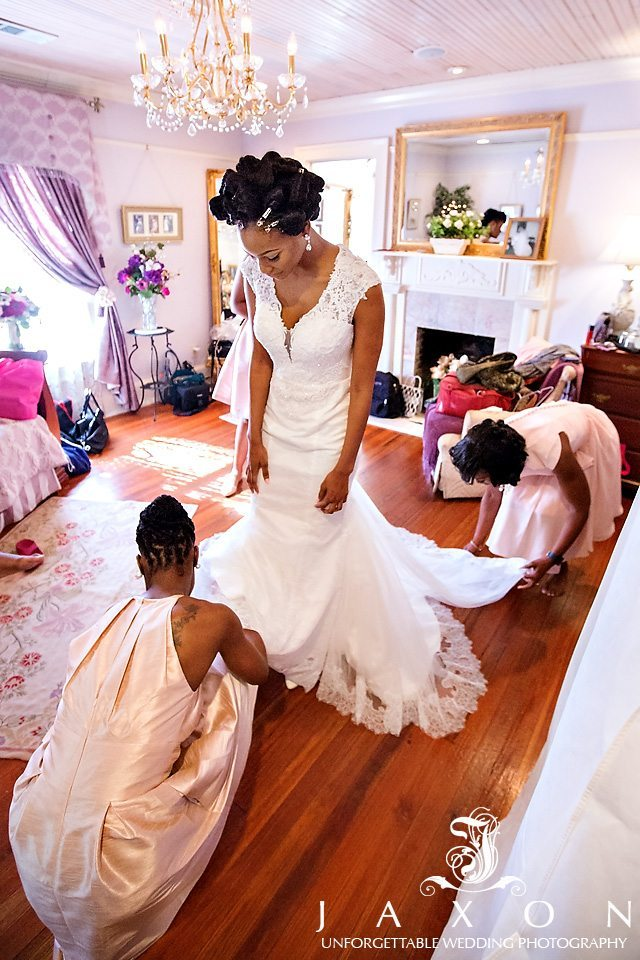 Two attendants assist bride in the bridal suite before her Carl House wedding