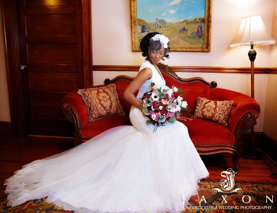 Bride in full regalia with bouquet sits in the center of red love seat with rolled arms.