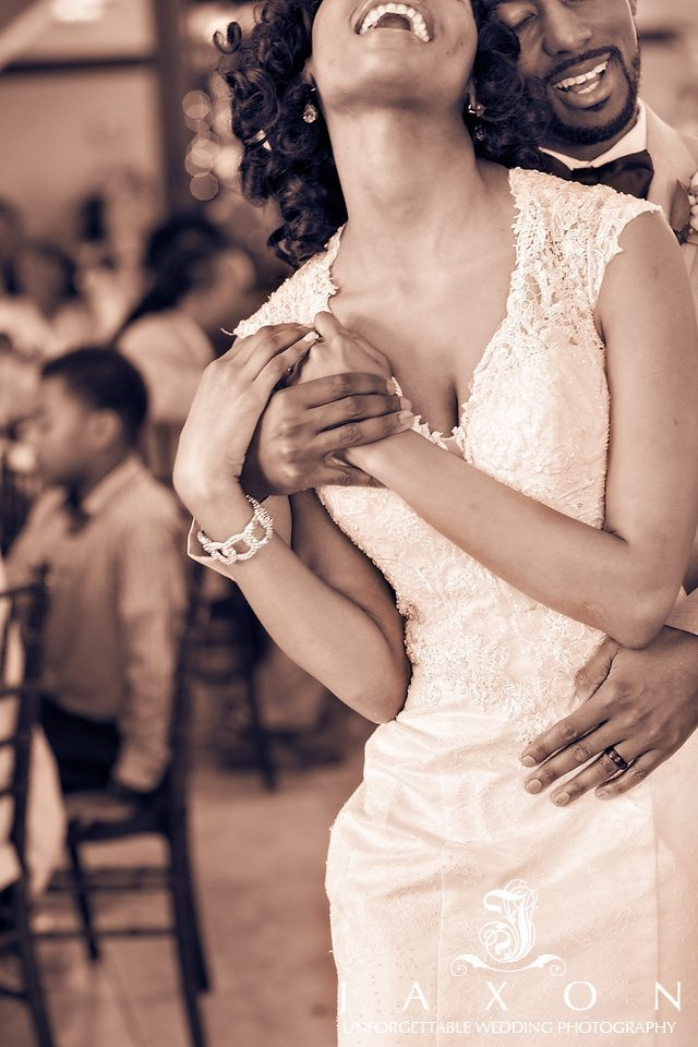 Sepia toned picture of bride and groom wrapped in each others embrace as they dance