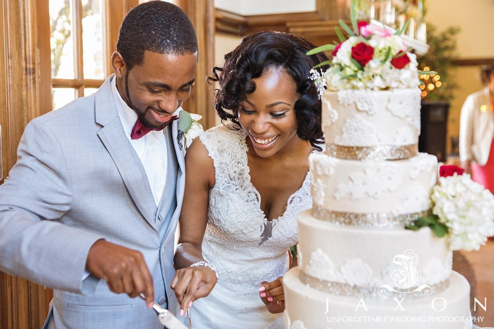 Bride and groom cuts their 5 tiered round wedding cake, decorated with lace and topped with flowers