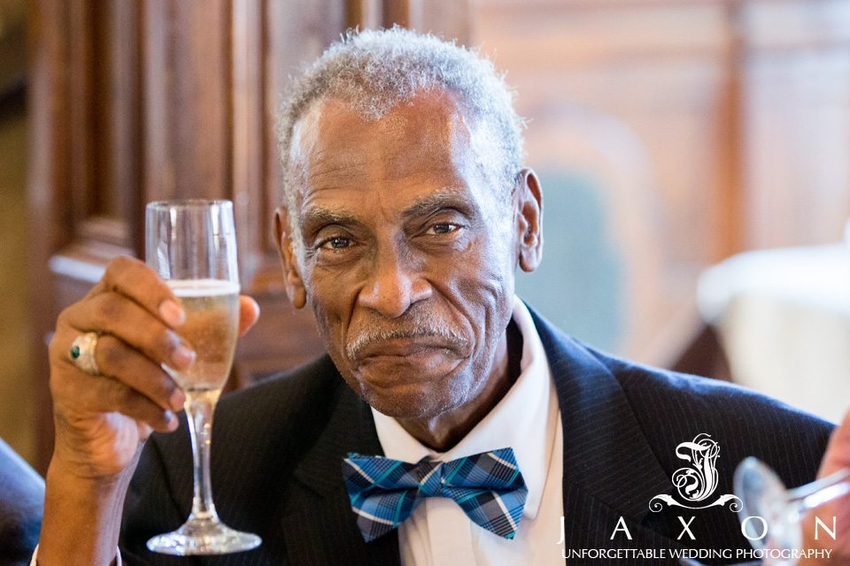 grandfather in blue and black bowtie toasts newly married couple during their carl house wedding reception