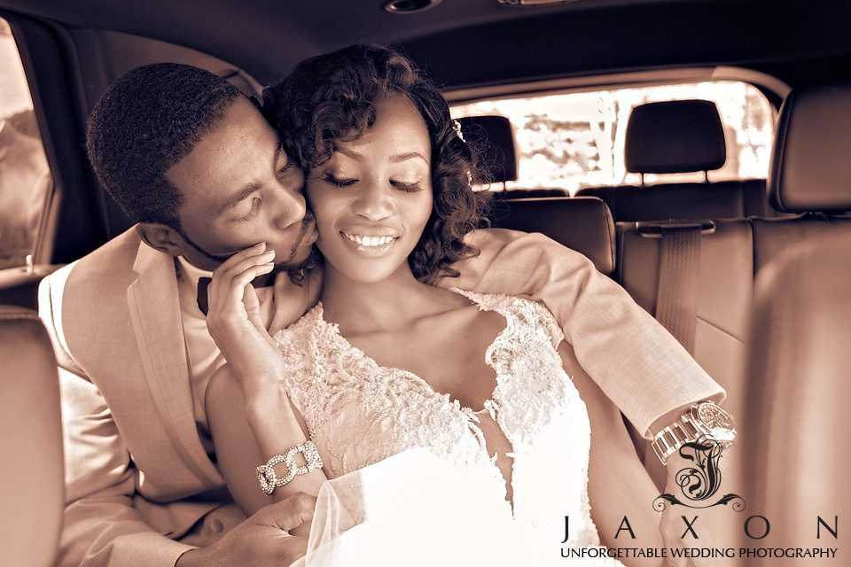 Groom kisses his bride as they embrace in the back of a limousine, photo highlights the lace beading surrounding plunging V-neckline of the dress