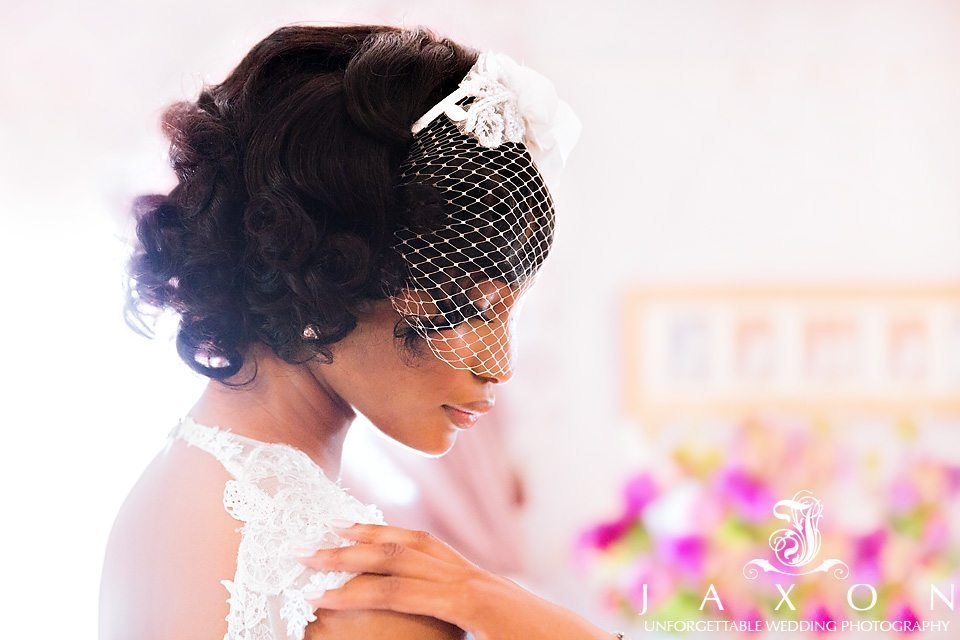Profile headshot of pride wearing birdcage veil also showing cutout in the back of the dress