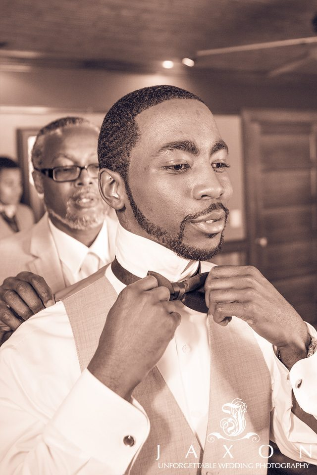Sepia image of groom as he adjusts his bow tie