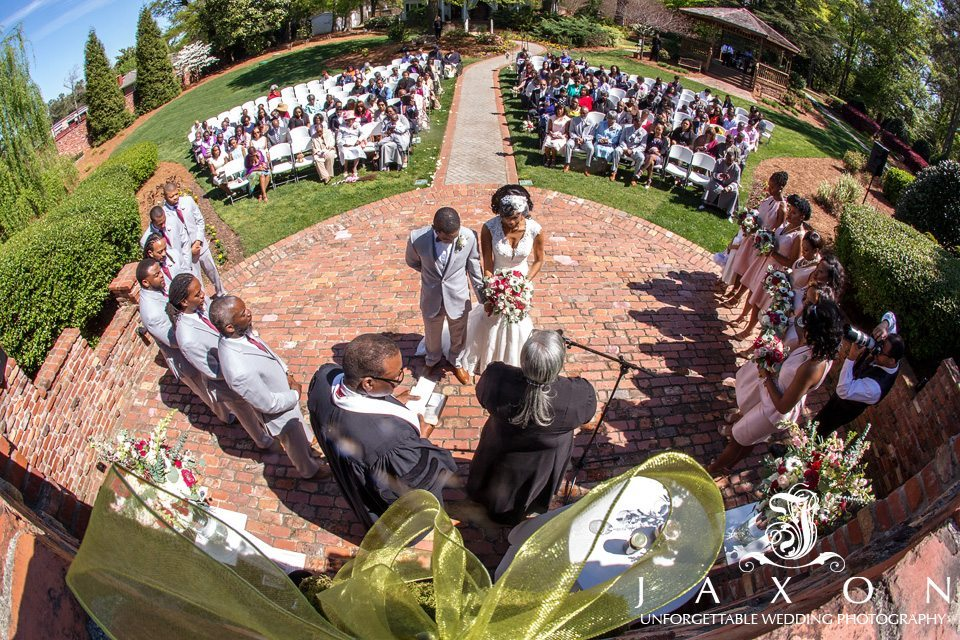 A fisheye lens angle view from high above the wedding ceremony in the gardens at the Carl House, the gazebo and mansion visible in background