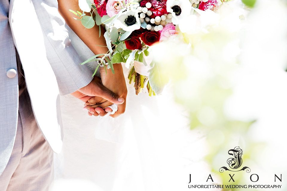 Close up of couple holding hands during wedding reception, her bracelet and bouquet draws attention to there hand kerchief wrapped finger