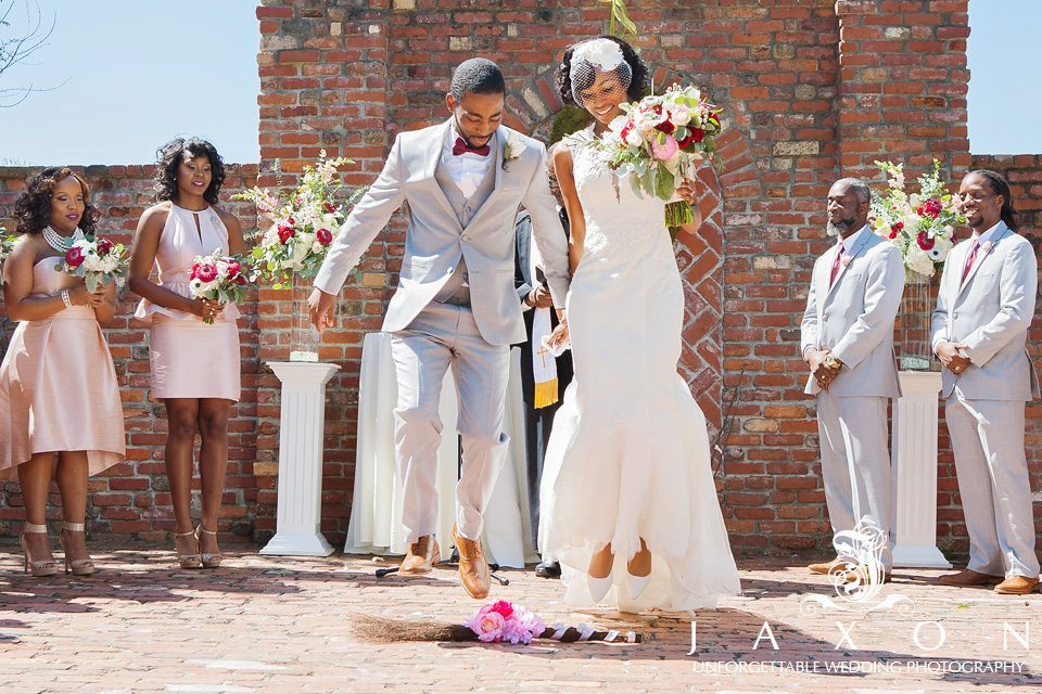 Newly married couple jumps beautifully decorated broom wrapped with a peach ribbon and flowers, at end of wedding ceremony
