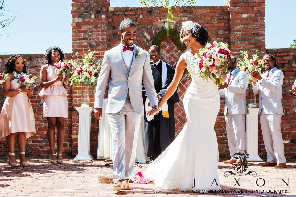 Jubilant couple smiles as they exits wedding ceremony