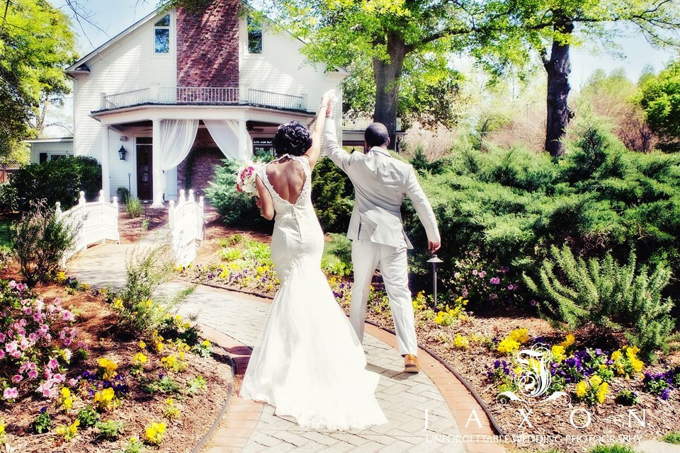 Couple raise their hands as they walk towards the bridge at the end of ceremony at their Carl House wedding