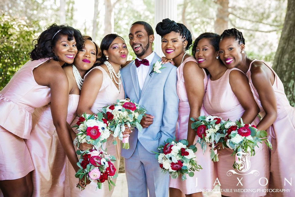 Groom in gray tux and plum bowtie surrounded by bridesmaids in peach short dresses and colorful bouquets