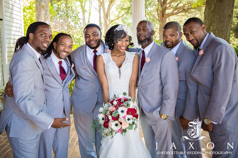 Bride surrounded by groomsmen in gray tuxes with pink boutonniere and plum long ties.