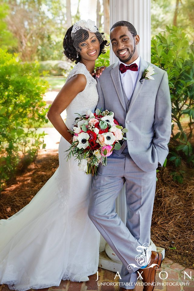 Full length portrait of bride and groom leaning at column atCarl House