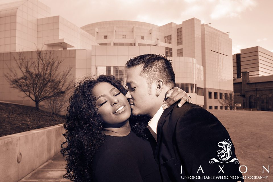 Sepia Portrait of couple embracing and kissing in-front of the High Museum of Art in Atlanta