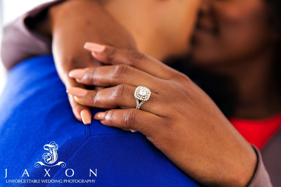 Closeup photograph of a Split shank duet halo diamond engagement ring on woman's hand, the couple kissing in the background