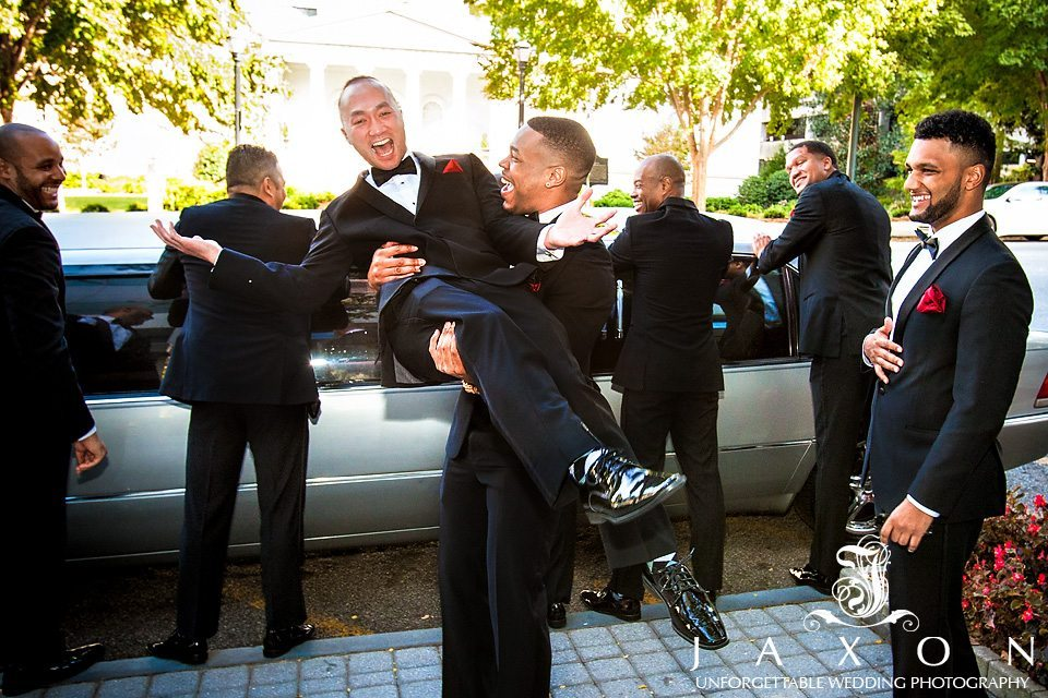 Groomsmen in black tuxedo, white shirts, black bowties and red boutonnieres have a little fun next to their limo on wedding day. In front of the Renaissance Midtown Atlanta Hotel