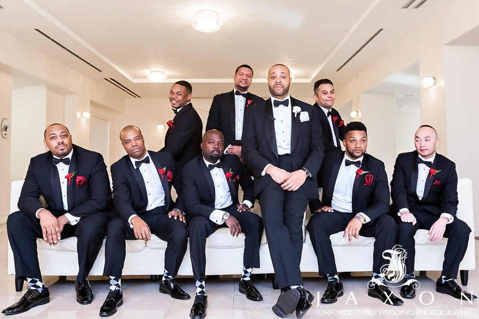 Groom and party dressed in black tuxedos white shirts, black bow ties with red boutonnieres and black, white and gray diamond socks, strike a pose on white couch at the Biltmore Ballrooms Atlanta before the wedding ceremony.