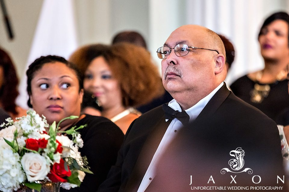 Father of the groom dressed in black tux, white shirt and black bowtie looks on intently at wedding ceremony at the Biltmore Ballrooms in Atlanta