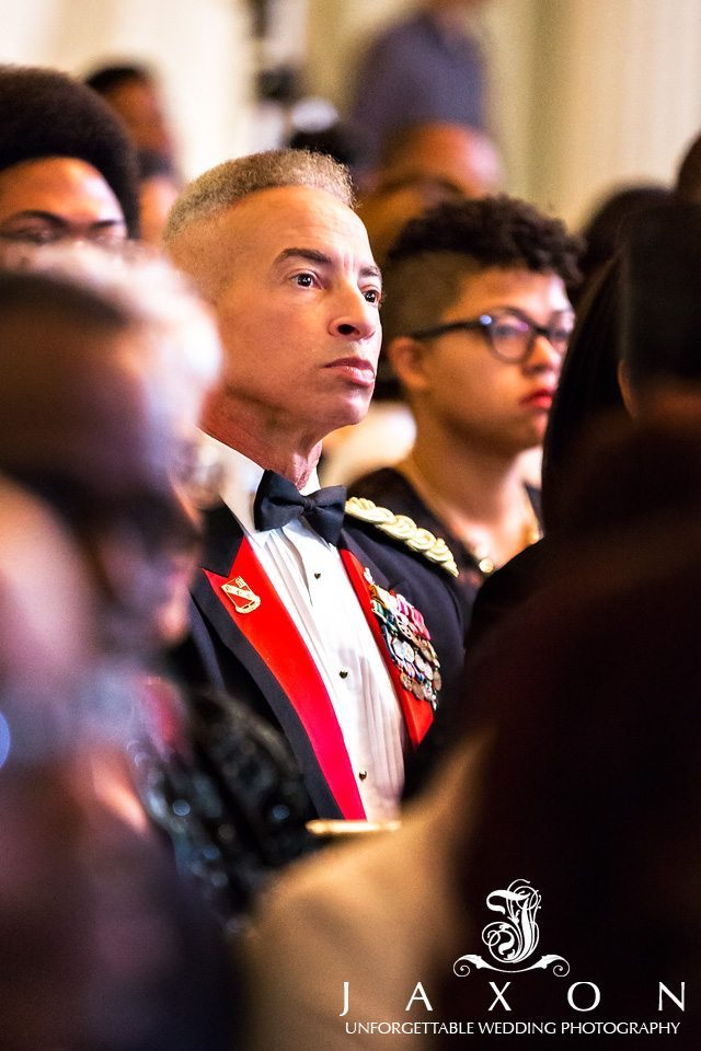 Man dressed in military style jacket with lots of medallions looks on intently at wedding proceedings