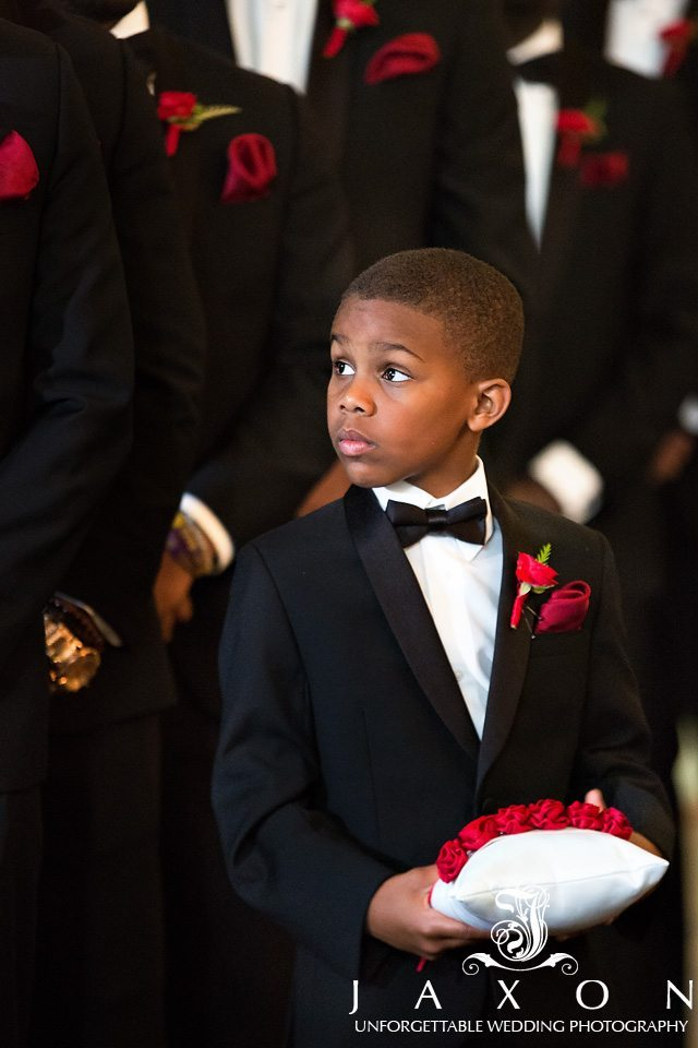Ring bearer dressed in a black tux, white shire, black bow tie red boutonniere and pocket square holds a white pillow decorated with red roses