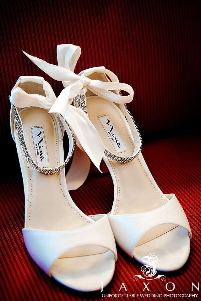 Photo of Nina NY Embellished Ankle Strap Sandal on red background